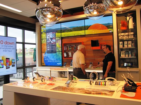 Pat Crilly, left, who was with a Kansas City, Kan., Area Chamber of Commerce group at the ribbon-cutting, viewed products on display at the new AT&T store. (Staff photo)