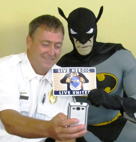 """Assistant Fire Chief John Peterson, left, takes a """"selfie"""" picture with Brince Rogers, right, playing Batman, at today's United Way of Wyandotte County campaign launch. A selfie contest was part of the events. (Staff photo)"""