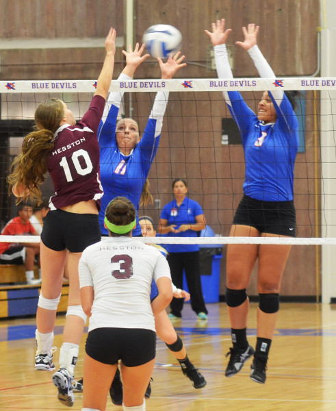 Sophomores Lily Thornberg (11) and Peyton Pender (3) attempt to block an attempted Hesston kill in KCKCC's 3-0 win in the home opener Wednesday. (KCKCC photo by Rodney Christensen)