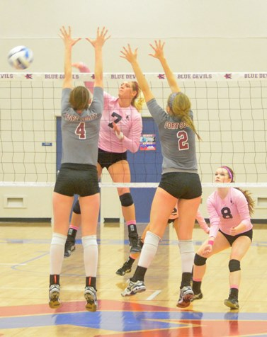 As teammate Lily Cullers (8) looks on, KCKCC outside hitter Blair Russell goes high to deliver a kill over two Fort Scott defenders in the Blue Devils' come-from-behind 3-1 win Wednesday. (KCKCC photo by Rodney Christensen)