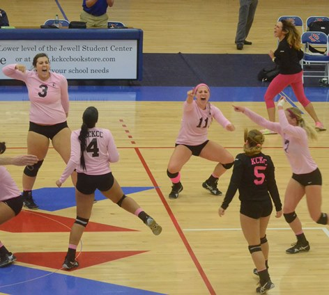 A game-winning kill by Jasdel Gonzalez (4) gave KCKCC a 3-1 win over Fort Scott Wednesday and set off a joyful celebration by teammates Peyton Pender (3), Lily Thornberg (11), Andrea Aparicio (5), Blair Russell (7) and coach Mary Bruno (upper right). (KCKCC photo by Rodney Christensen)