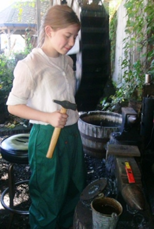 Lily Cody worked as an apprentice blacksmith at the Renaissance Festival recently. (Photo by William Crum)