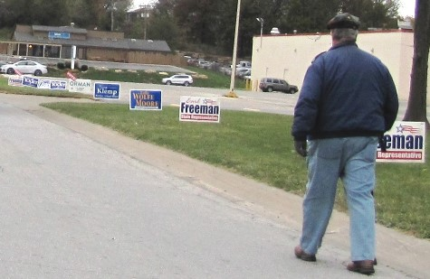 A man walked along North 79th Street, north of State Avenue in Kansas City, Kan.,, on Election Day, where campaign signs lined the street leading to a polling place.