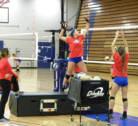 KCKCC coach Mary Bruno, left, keeps a watchful eye on co-captain Blair Russell's hitting form, one of several fundamentals the Lady Blue Devils undergo daily in preparation for the NJCAA National volleyball tournament in Phoenix, Ariz. Thursday. (KCKCC photo by Alan Hoskins)