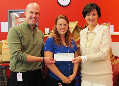 Ann Murguia, executive director of the Argentine Neighborhood Development Association, right, presented an ANDA check for $200 to a holiday food drive being sponsored at the Argentine Save-a-Lot grocery store. Representing the grocery were Jeff Turnbough, left, district manager, and Jessica Wilson, center, store manager. (Staff photo)