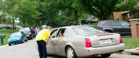 Cars were parked along one side of the street in this Indian Woods subdivision near a church that is holding a mobile food pantry on Saturdays, in this file photo from August. There were persons assigned to direct traffic. (File photo)