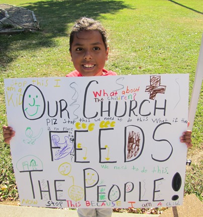 Alexandra Arevalo, 7, held a poster she made about her church providing food for people.