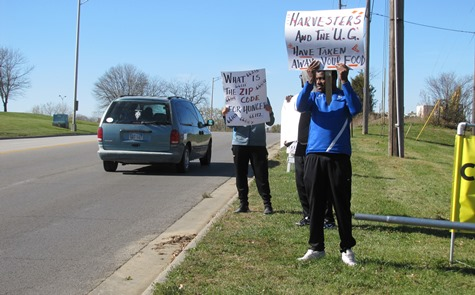 "College student volunteers held up signs Saturday outside a food distribution site at the CrossRoads Family Church, 8822 Parallel Parkway. One of the signs reads, ""What is the Zip Code for hunger?"" A food distribution truck did not go to this site after the Unified Government told Harvesters that the UG thought the traffic from the food distribution site would be a safety hazard."