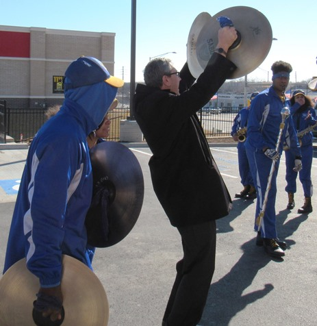 Stephen Graves, vice president of operations at Krispy Kreme, played the cymbals with the Schlagle marching band today to celebrate the opening of the 1,000th Krispy Kreme store worldwide in Kansas City, Kan. (Staff photo by Mary Rupert)