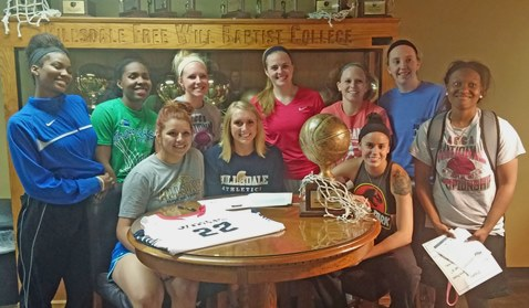 Kansas City Kansas Community College forward Julia Garrard, seated, center, was surrounded by her new teammates as she signed a letter of intent to continue her basketball career at Hillsdale Free Will Baptist College in Moore, Okla.  (Photo from KCKCC)