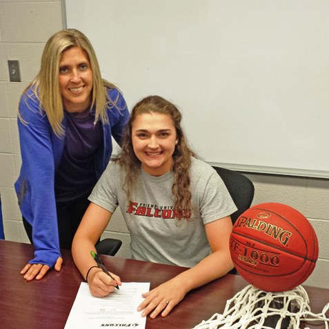 With coach Valerie Stambersky as her witness, Kansas City Kansas Community College's all-time leader in career assists Cassidy Harbert signed a letter of intent to continue her basketball career at Friends University in her home town of Wichita. (KCKCC photo by Rodney Christensen)