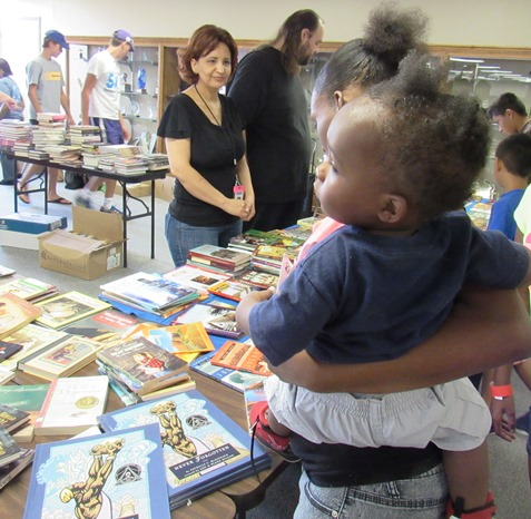 Children attending the Back-to-School Fair today could receive free books from the Kansas City, Kan., Public Library. Staffing a booth for the library, at the KCKCC  fair location, were Maria Munoz and Joseph Smith, from the West Wyandotte Library branch. (Staff photo by Mary Rupert)