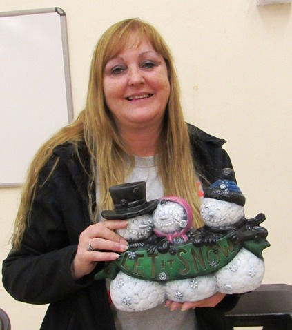 "Debby Smith Porter held a ceramics figure she made that says, ""Let it Snow,"" at the Eisenhower Craft Fair on Saturday at Eisenhower Recreation Center, Kansas City, Kan. (Staff photo)"
