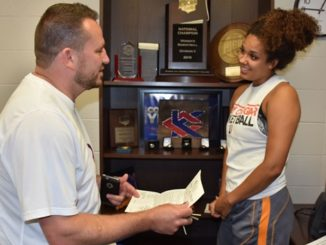 KCKCC women's basketball coach Joe McKinstry and forward Brooklyn Wagler go over Wagler's itinerary for her participation this weekend in the NJCAA Women's Basketball Coaches All-Star games in Dustin, Fla. (KCKCC photo by Alan Hoskins)