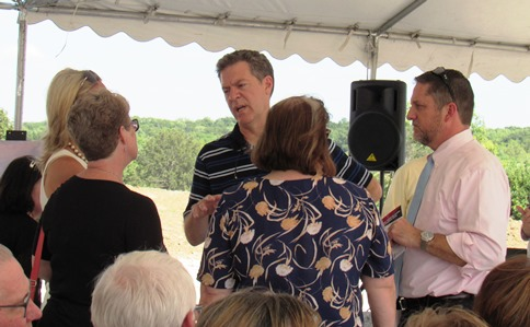 Before the groundbreaking, Gov. Sam Brownback visited with Mayor Mark Holland, right, and members of the Unified Government Commission. (Staff photo by Mary Rupert)