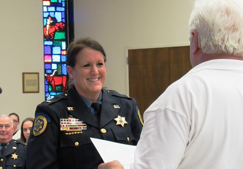 Stephen Barnhart awarded a presidential certificate to Lt. Kelli Bailiff of the Wyandotte County Sheriff's Department for her volunteer service on Thursday night at the Unified Government Commission meeting. (Staff photo by Mary Rupert)