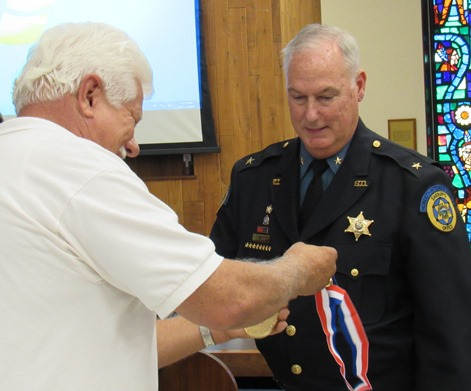 Stephen Barnhart prepared to bestow a medallion for volunteer service to Sheriff Don Ash at Thursday night's Unified Government Commission meeting. (Staff photo by Mary Rupert)