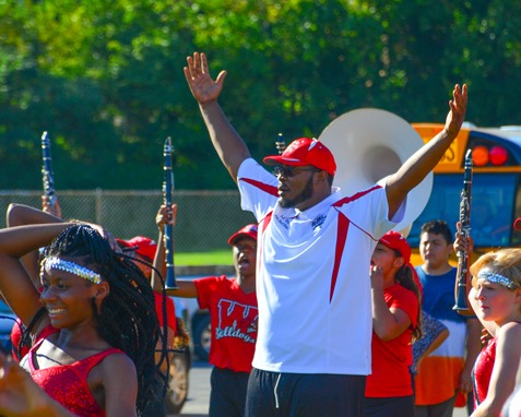 Deandre Tatum, assistant director of the Wyandotte High School Marching Band, raised his arms in celebration at the conclusion of a Battle of the Bands with Washington High School following the Leavenworth Road Parade. (Photo by Brian Turrel)
