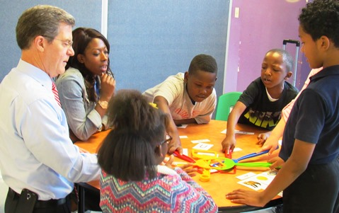 Gov. Sam Brownback, left, participated in activities with young students Thursday at the Boys and Girls Club in Kansas City, Kan. (Staff photo)