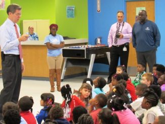 Gov. Sam Brownback, left, on Thursday told young students at the Boys and Girls Club in Kansas City, Kan., that learning to read would open doors for them all over the world.  (Staff photo)