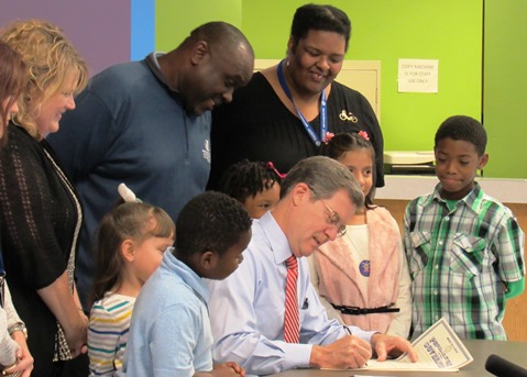 Gov. Sam Brownback signed a proclamation for Lights On Afterschool Day in Kansas on Thursday at the Boys and Girls Club in Kansas City, Kan. (Staff photo)