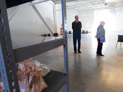 A few people dropped off sacks of groceries and placed them on the empty shelves at the new Cross-Lines building, which will include a food pantry. (Staff photo by Mary Rupert)